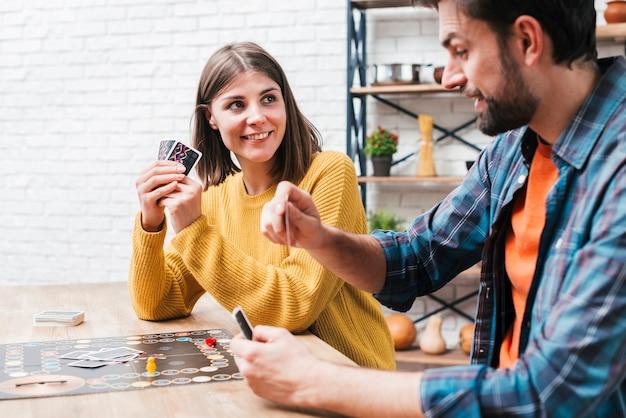 Jeune couple jouant au jeu de société sur une table en bois Photo gratuit