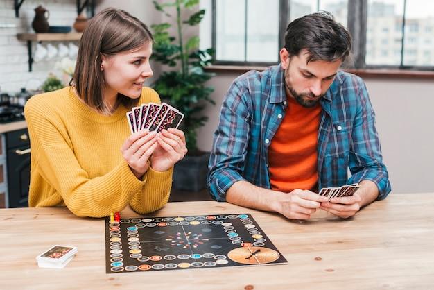 Jeune couple jouant au plateau de jeu sur un bureau en bois Photo gratuit