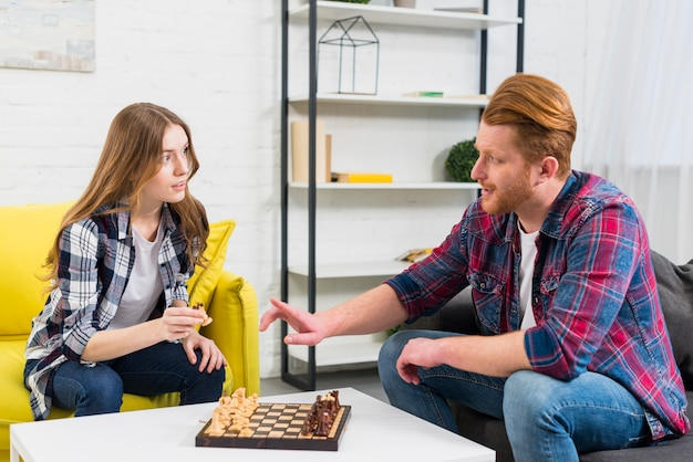 Jeune couple jouant aux échecs à la maison Photo gratuit