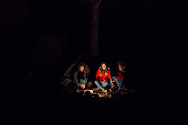 Jeune couple et leur ami profitant du camping de nuit Photo gratuit