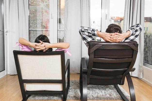 Jeune couple avec leurs mains derrière la tête, assis sur une chaise à la maison Photo gratuit