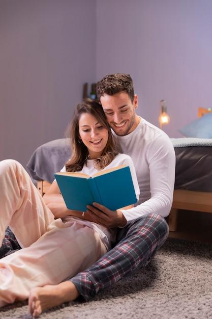 Jeune couple lisant ensemble au lit Photo gratuit