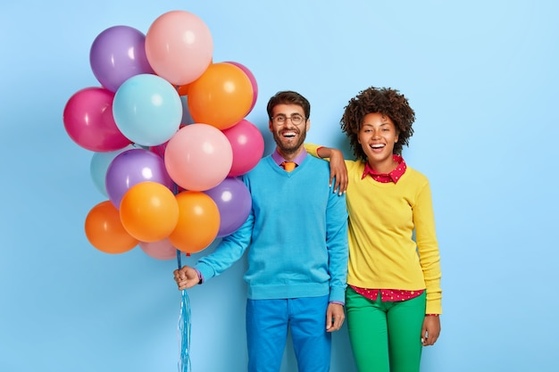 Jeune Couple Lors D'une Fête Posant Avec Des Ballons Photo gratuit