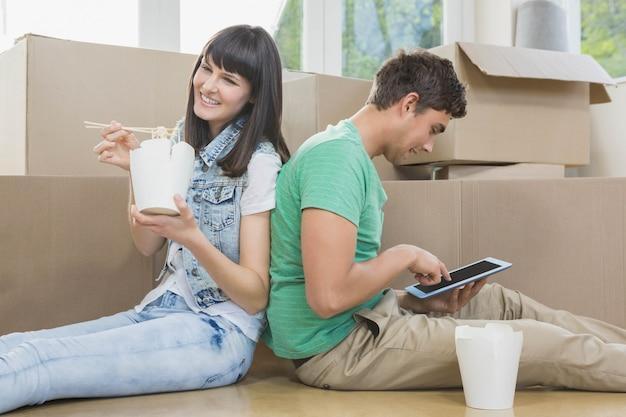 Jeune couple mangeant des nouilles et utilisant une tablette numérique dans leur nouvelle maison Photo Premium