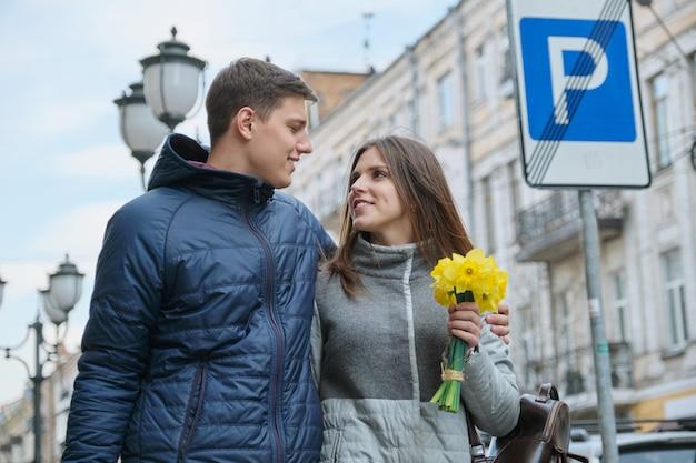Jeune couple marchant avec bouquet de fleurs printanières jaune Photo Premium