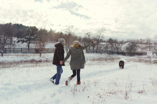 Jeune Couple Marchant Avec Un Chien Dans Une Journée D'hiver Photo gratuit