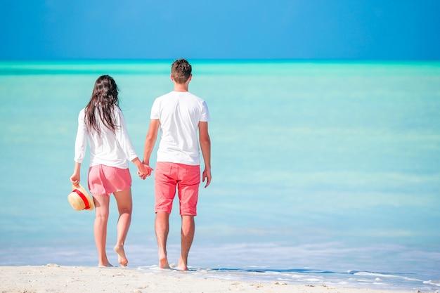 Jeune couple marchant sur une plage tropicale Photo Premium
