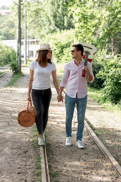 Jeune couple marchant sur une voie ferrée Photo gratuit