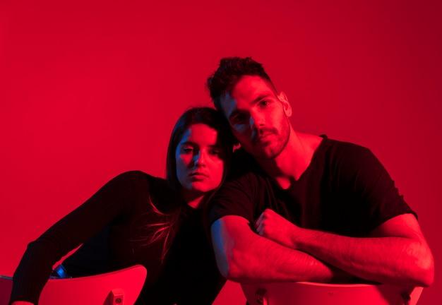 Jeune couple en noir assis sur des chaises Photo gratuit