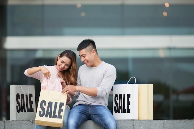 Jeune couple partageant des achats en vente Photo gratuit