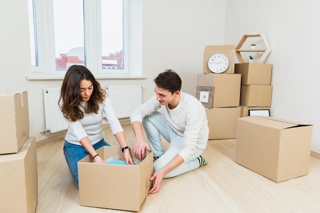 Jeune couple, passer, nouveau lieu, séance, près, carton, déballage, plats Photo gratuit