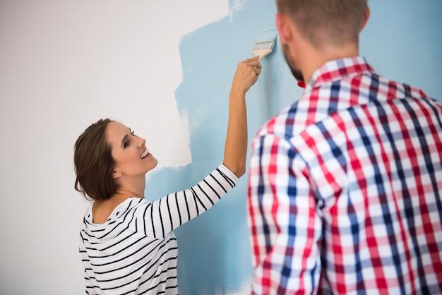 Jeune Couple Peignant Un Mur Bleu Photo gratuit