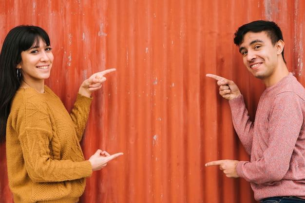 Jeune couple pointant vers la clôture orange Photo gratuit