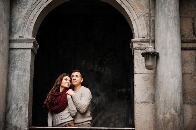 Jeune couple, porter, attaché, chandails chauds, étreindre, amour, vieux, cour, arc, colonnes, ville Photo Premium