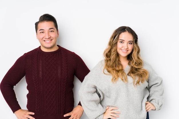 Jeune Couple Posant Dans Un Mur Blanc Confiant En Gardant Les Mains Sur Les Hanches. Photo Premium