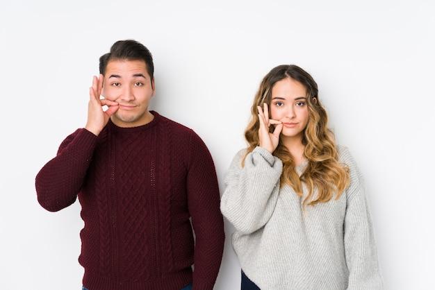 Jeune Couple Posant Dans Un Mur Blanc Avec Les Doigts Sur Les Lèvres Gardant Un Secret. Photo Premium