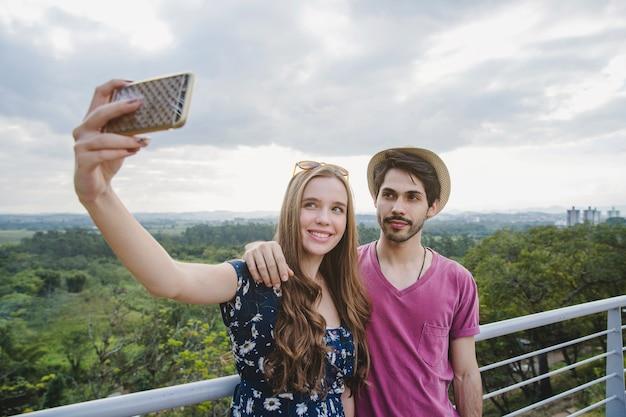 Jeune couple prenant selfie sur la plateforme d'observation Photo gratuit