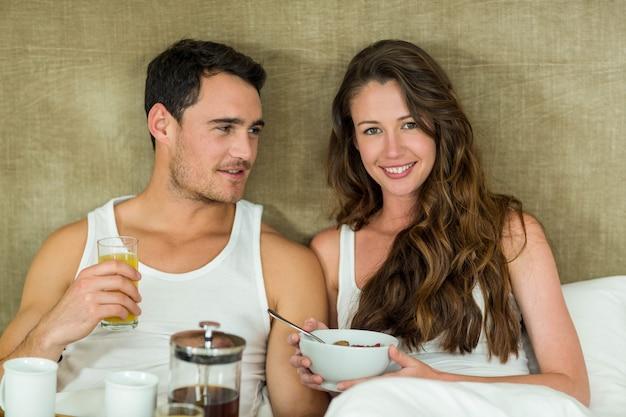 Jeune couple prenant son petit déjeuner au lit dans la chambre Photo Premium