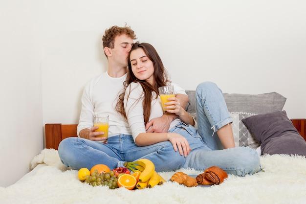 Jeune couple prenant son petit déjeuner au lit Photo gratuit