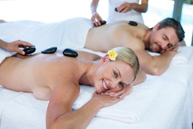 Jeune Couple Recevant Un Massage Aux Pierres Chaudes D'un Masseur Photo Premium