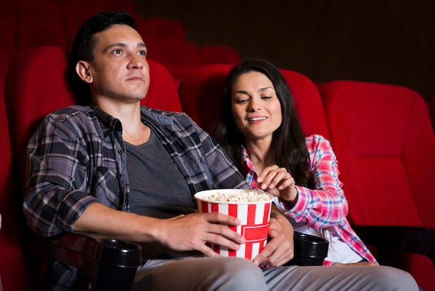 Jeune couple en regardant un film au cinéma Photo gratuit
