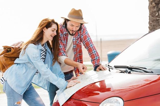 Jeune couple, regarder, feuille route, sur, voiture rouge Photo gratuit