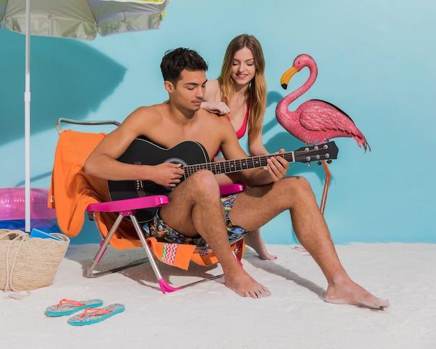 Jeune couple, reposer, plage, studio Photo gratuit