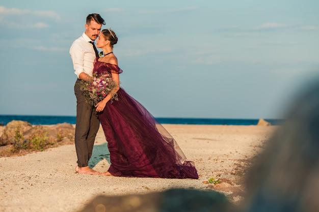 Jeune Couple Romantique Se Détendre Sur La Plage En Regardant Le Coucher Du Soleil Photo gratuit