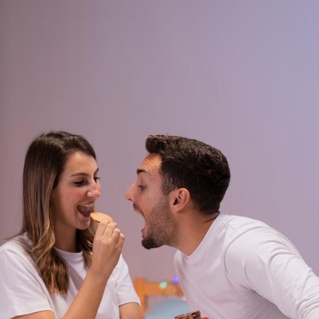 Jeune couple s'amuse au lit Photo gratuit