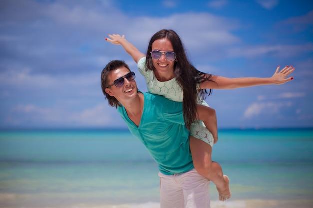 Jeune couple s'amuser sur la plage de sable blanc Photo Premium