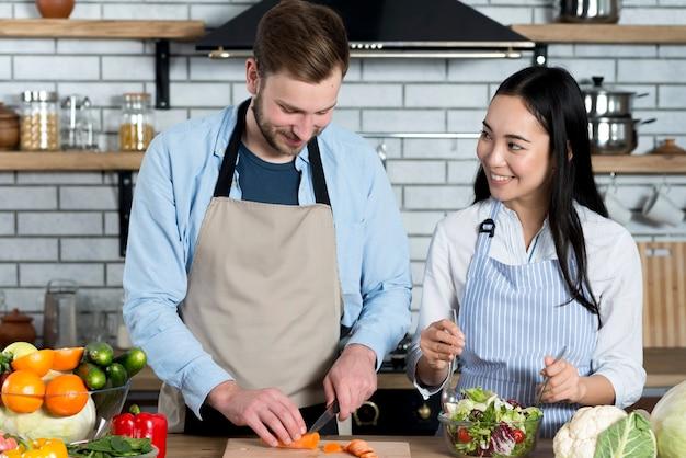 Jeune couple s'amuser tout en préparant un repas dans la cuisine Photo gratuit