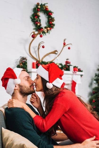 Jeune couple s'embrassant sur le canapé Photo gratuit