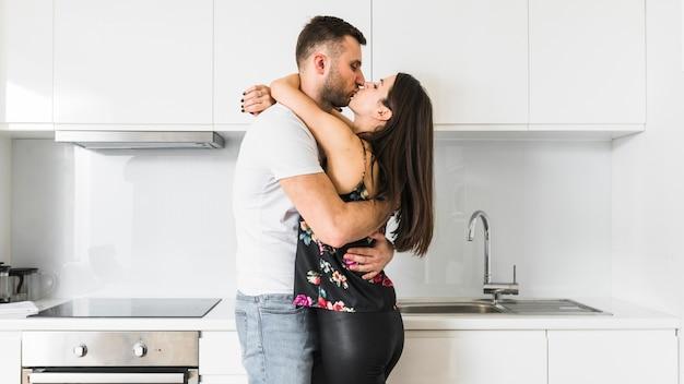 Jeune couple s'embrassant dans la cuisine Photo gratuit