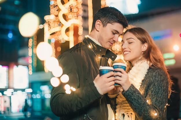 Jeune Couple S'embrassant Et étreignant En Plein Air Dans La Rue De Nuit Au Moment De Noël Photo gratuit