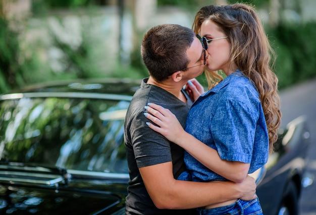 Jeune couple s'embrassant habillé dans un style décontracté se tient devant une vieille voiture rétro de sport Photo gratuit