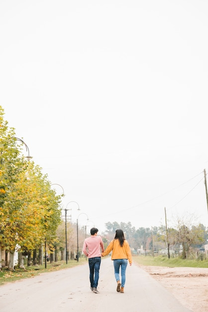 Jeune couple se promenant le long de la route Photo gratuit