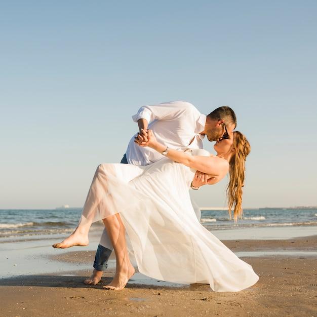 Jeune couple se tenant la main, donnant pose en s'embrassant à la plage Photo gratuit