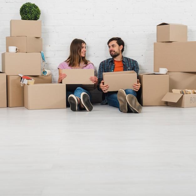 Jeune couple, séance plancher, tenue, carton, main, regarder, autre Photo gratuit