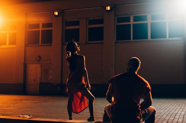 Un jeune couple sexy amoureux pose dans la rue de nuit de la ville. Photo gratuit