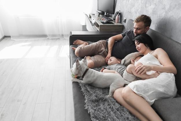 Jeune couple avec son fils et son chien blanc allongé sur un canapé gris à la maison Photo gratuit