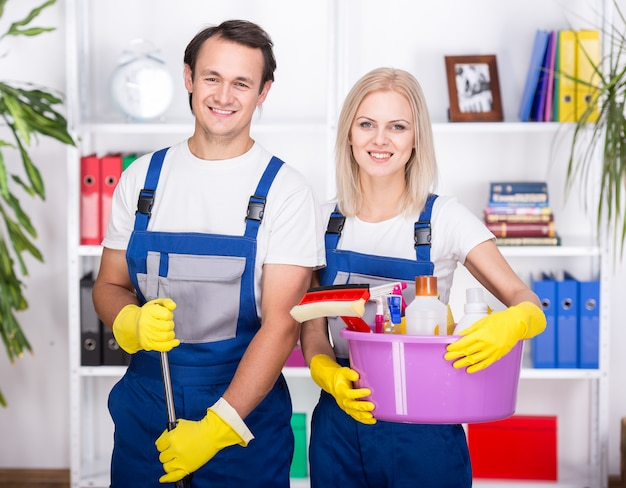 Jeune couple souriant tient des outils de nettoyage. Photo Premium