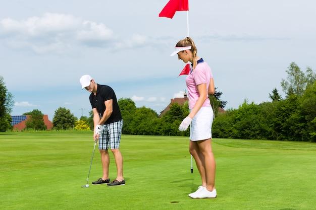 Jeune couple sportif jouant au golf sur un parcours Photo Premium