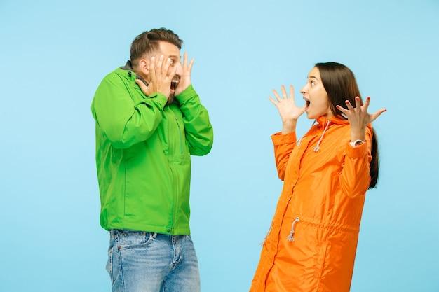 Jeune Couple Surpris Au Studio En Vestes D'automne Isolé Sur Bleu. émotions Négatives Humaines. Concept Du Temps Froid. Concepts De Mode Féminine Et Masculine Photo gratuit