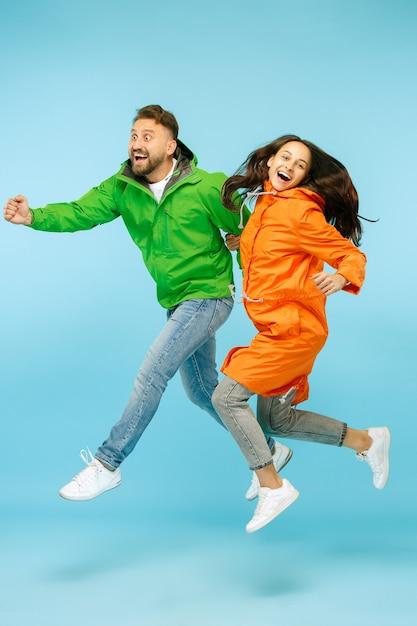 Jeune Couple Surpris Au Studio En Vestes D'automne Isolé Sur Bleu. Humaines émotions Positives Heureuses. Concept Du Temps Froid. Concepts De Mode Féminine Et Masculine Photo gratuit