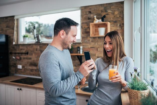 Jeune couple surpris par les bonnes nouvelles du matin dans la cuisine. Photo Premium