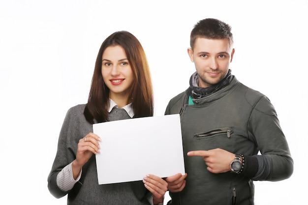 Jeune couple tenant une feuille de papier vierge. Photo Premium