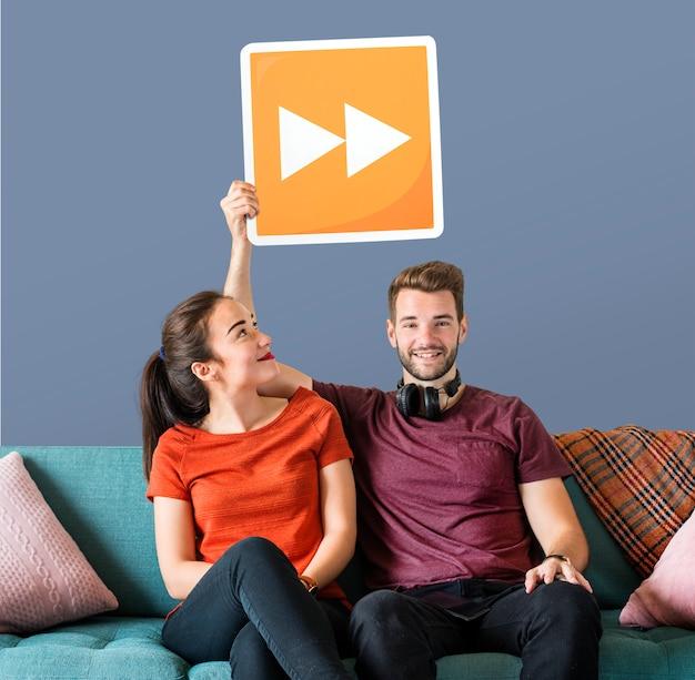 Jeune couple tenant une icône de bouton Photo gratuit
