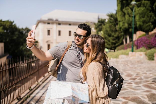 Jeune couple, vacances, prendre, autoportrait, à, téléphone portable Photo gratuit