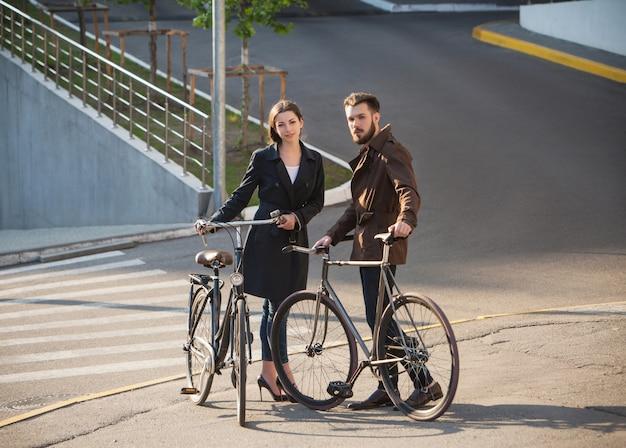 Jeune Couple Avec Un Vélo En Face De La Ville Photo gratuit