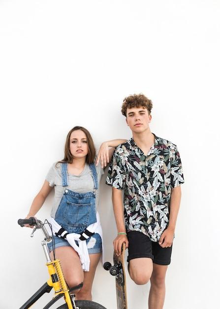Jeune couple avec vélo et skateboard debout sur fond blanc Photo gratuit